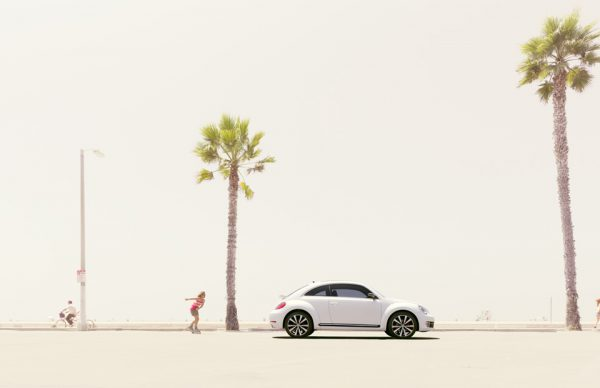 Retouched Volkswagen bettle on coast with girl rollerblading behind